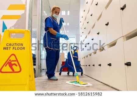 A cleaner with a mask on her face cleans the floor with the mop.Caution wet floor sign close up Stock foto ©