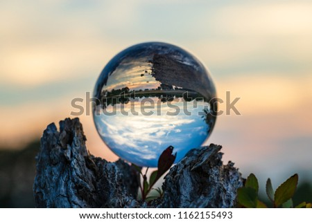 A clear glass ball sitting on a tree branch with a sunset able to be seen through it with a silky smooth, bokeh background.
