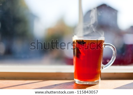 A clear glass cup of hot tea with a floating tea bag and a anise star with steam rising. blurred domestic background.