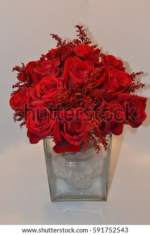 A clear glass vase holds a brilliant bouquet of ruby red roses and floral leaves with a white back ground.  #591752543