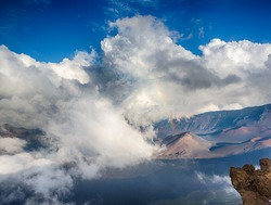 A clearing storm creates a rainbow over the Haleakala Crater on Maui