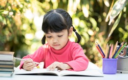 A clever child Asian girl  doing homework and drawing painting the color on the art book. Kid enjoy learning with happiness at home. Clever, genius, education and smart learning concept.