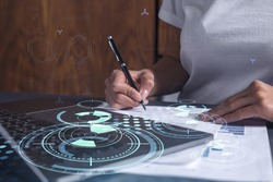 A client is signing a contract to create a new software to present it in start up conference and gain investments to create a product. Technological graph over the desk. Women in business concept.