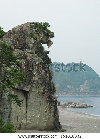 A cliff over a sandy beach with water and a larger cliff in the background.
