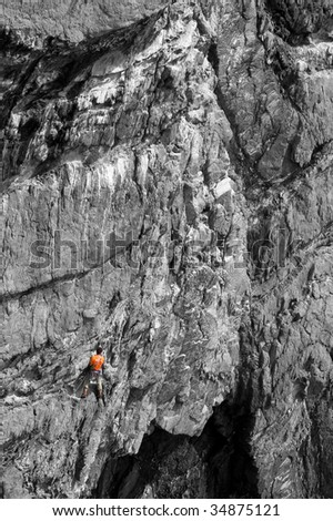 A climber clad in bright orange colour on a B&W rock, good background for \