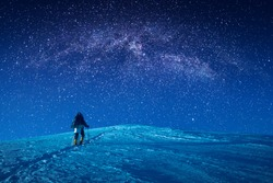 A climber climbs up a snowy slope at night. Milky way in a starry sky above the mountain top.