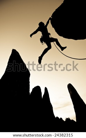 A climber dangles from the edge of an overhanging rock in The Sierra Nevada Mountains, California.