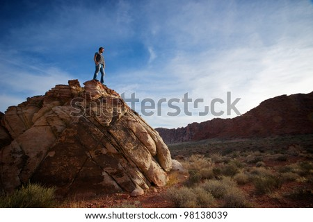 A climber/hiker stands atop large boulders and gazes into the wilderness of Red Rocks Canyon State Park in Las Vegas, Nevada.