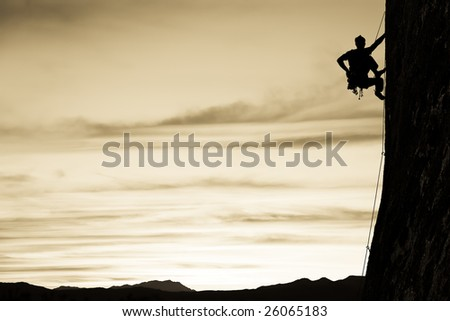 A climber is silhouetted as he clings to a steep rock face in Joshua Tree National Park, California.