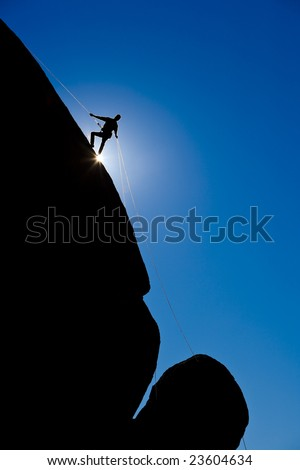 A climber is silhouetted as rappels down a steep rock face in the Sierra Nevada Mountains, California.