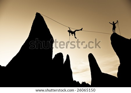A climber is silhouetted as she pulls herself across a gap between two pinnacles, in the Sierra Nevada  Mountains, California.