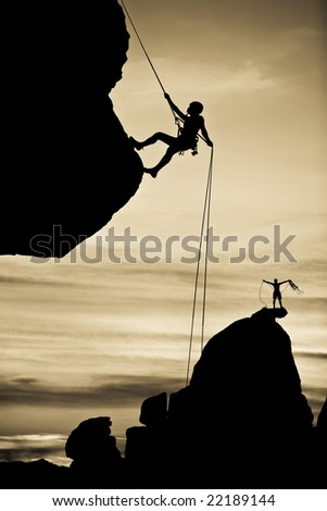 A climber is silhouetted as she rappels from the summit of a rock spire in The Sierra Nevada Mountains, California, after a successful ascent.