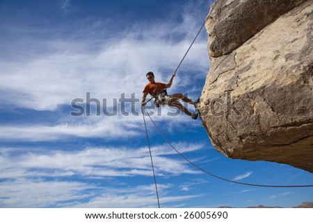 A climber rappelling from the summit of a rock spire after a successful ascent in The Sierra Nevada Mountains, California.