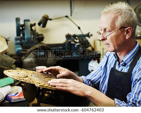 A clock maker adjusting the hands on the face of an antique clock