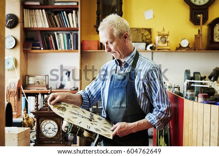 A clock maker holding an antique clock face looking at it