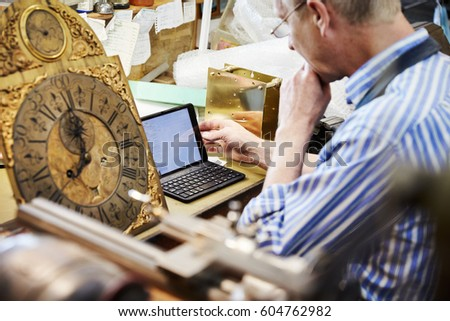 A clock maker in his workshop using a laptop Antique clock face