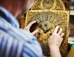 A clock maker moving the hands on an antique clock, repairing and resetting the clock Over the shoulder view