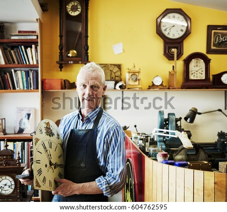 A clock repairer holding an antique clock face in his workshop