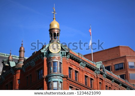 A clock tower with small golden dome on it, on one of the corners of a vintage red building with many windows and blue fixtures and an American flag on it. Capitol hill, Washington D.C.
