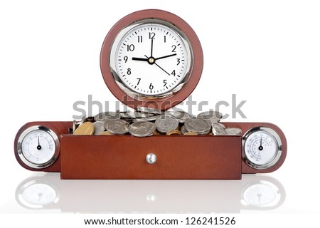 A clock with a wooden frame contains a drawer filled with coins.