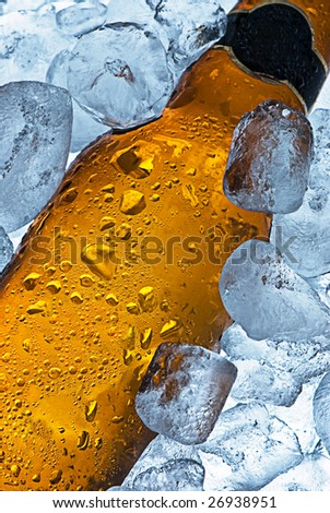 A close crop of a beer bottle sitting in a container of ice. Cold and ready to drink.