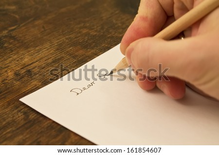 A close photo of a persons writing a letter with a pencil.