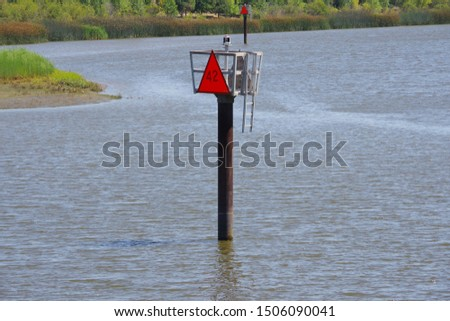 A close sectional view of the Napa river in a curve with sign posts for ship and boat traffic