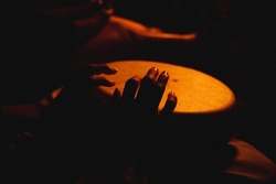 A close shot of the hands of a man playing a melody on ethnic drums