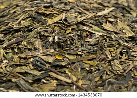 A close-up and detailed studio product shot of a bunch of dried and loose Chinese green tea leaves.