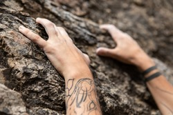 A close up and selective focus view of caucasian hands struggling to grip a natural stone face, parallels with real world struggles. With copy space