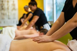 A close up and side view on a row of massage pupils practicing in a classroom setting, giving back massages, with blurry pupils and copy space