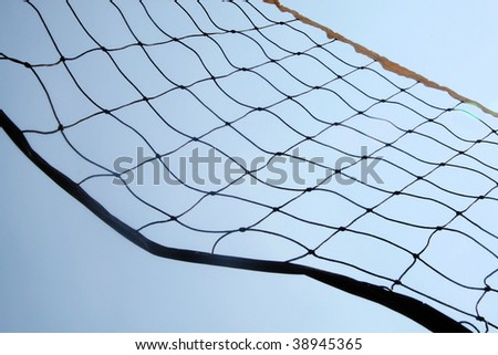 A close up beach volley ball net in front of sky.