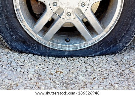 a close up, centered view of a flat car tire that has popped on a gravel road.  Room for copy-space.