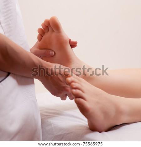 A close-up detail of a masseur giving a foot massage