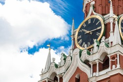 A close-up Detail of the Kremlin's Spasskaya tower on red square on a Sunny day against a bright blue sky. Large clock and chimes on the Spasskaya tower.