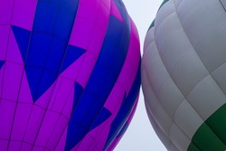 A close-up detail shot of a purple hot air balloon with blue arrows touching a green and gray one