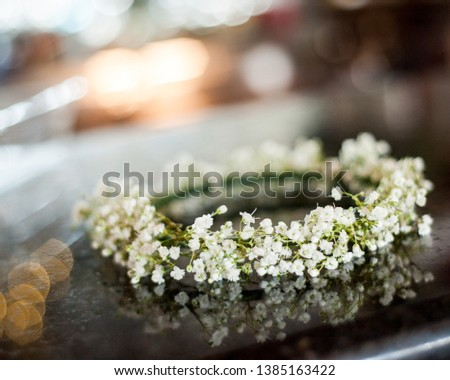 A close-up detail shot of the flower girl's hairpiece made of babies breath flowers sitting on a table top at the wedding venue Sunny Meade, in South Louisiana.