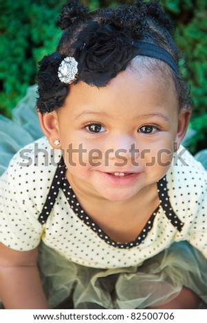 A close-up head shot of an eleven month old female baby in a polka dot tutu.