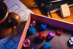 A close-up image of a pink dice tray filled with multicolor role playing dice, a ceramic drinking jar, a black notebook, a black pencil and an eraser