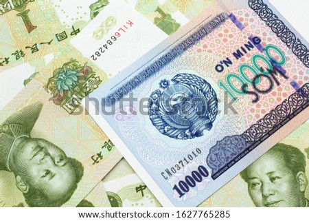 A close up image of a ten thousand Uzbek som bank note on a background of green, Chinese one yuan bills bills in macro