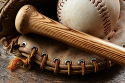 A close up image of an old used baseball, baseball bat, and baseball glove.