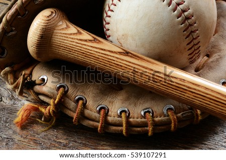 A close up image of an old used baseball, baseball bat, and baseball glove.