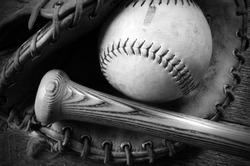 A close up image of an old used baseball, baseball glove, and wooden bat.