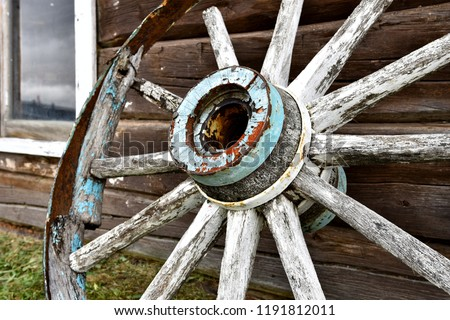 A close up image of an old wooden wagon wheel leaning on a log cabin.