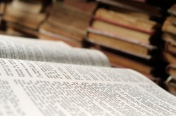 A close up image of an opened bible with various old foxed books in the background.