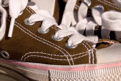 A close up image of canvas tennis shoes shows the detail of the eyelets and shoelaces.