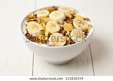 A close up image of cereal bowl with slice bananas on a wooden background