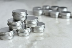 A close up image of several small silver metal sample tins on a white marble table top.