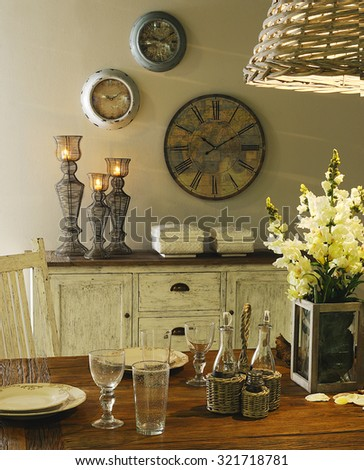 a close up in a table with dinnerware set and with a buffet on background with candles and clocks on the wall #321718781