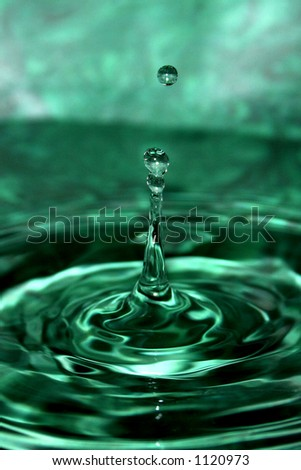 A close-up/macro of a green splashing water droplet with ripples flowing out.  A smaller drop is suspended in air above the main splash.